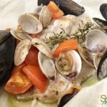 Filetto di pesce serra al cartoccio con frutti di mare e pomodorini